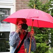 ragazza fotografa con ombrello mentre piove