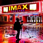 Riflessi di neon sul bagnato e fotografo con il treppiedi