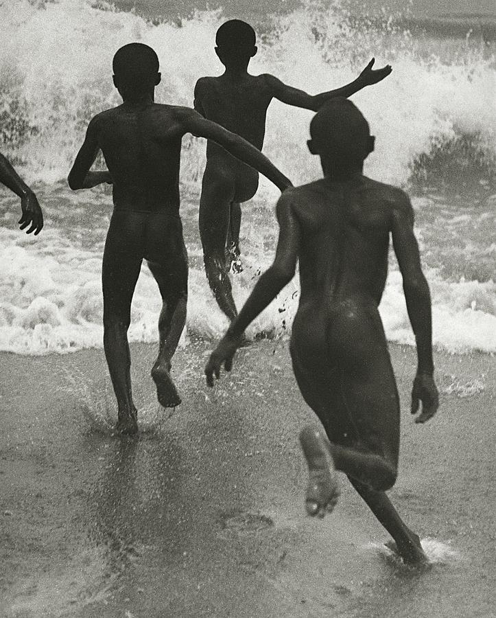 Tre ragazzi neri corrono verso l'acqua