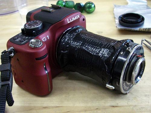 Una vecchia lente adattata, per mezzo di tanto nastro telato nero, ad un apparecchio digitale