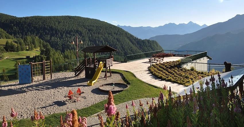 Parco giochi di Chamois con la vista delle montagne verso il Parco del Gran Paradiso